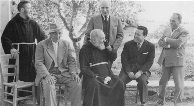 Padre Pio with people in the garden